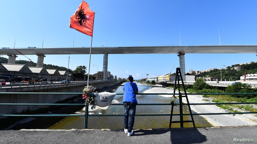 FILE - A man stands next to flowers and a t-shirt with the picture of a victim of the collapse of the Morandi bridge, as static testing operations are performed on the bridge ahead of its inauguration, in Genoa, Italy, July 19, 2020.