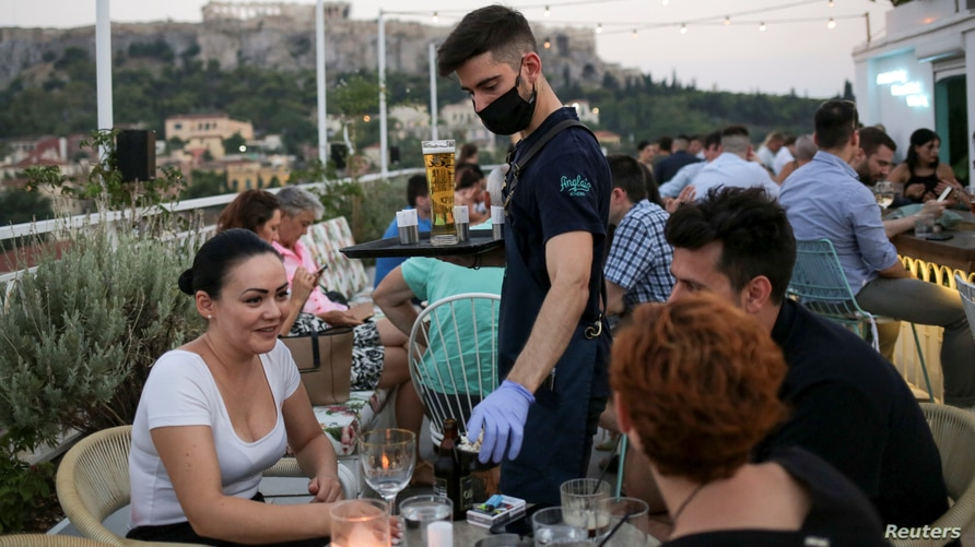 A waiter wears a protective face mask serves customers in a bar, amid the spread of the coronavirus disease (COVID-19), in Athens, Greece, Aug. 1, 2020.