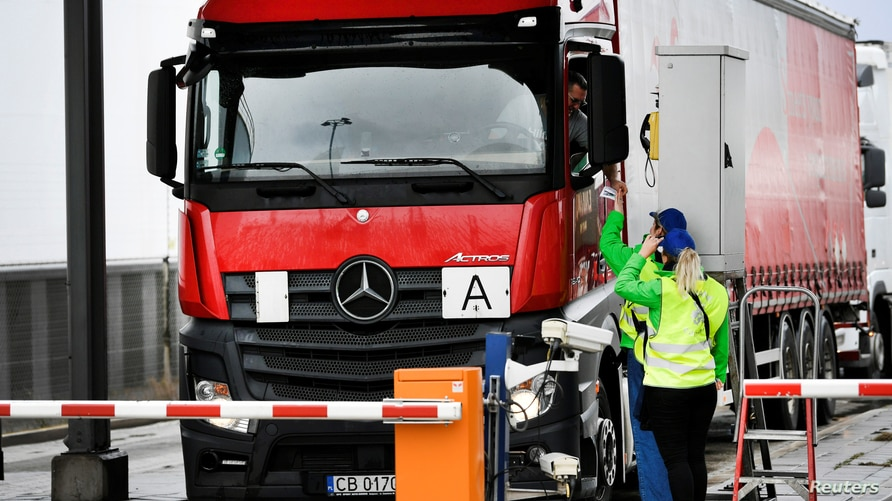 Ferry terminal workers from the Brexit info-team give a flyer to a truck driver to review that cargo can be transported quickly via Dutch ports after the Brexit, in Vlaardingen, Netherlands, March 13, 2019.