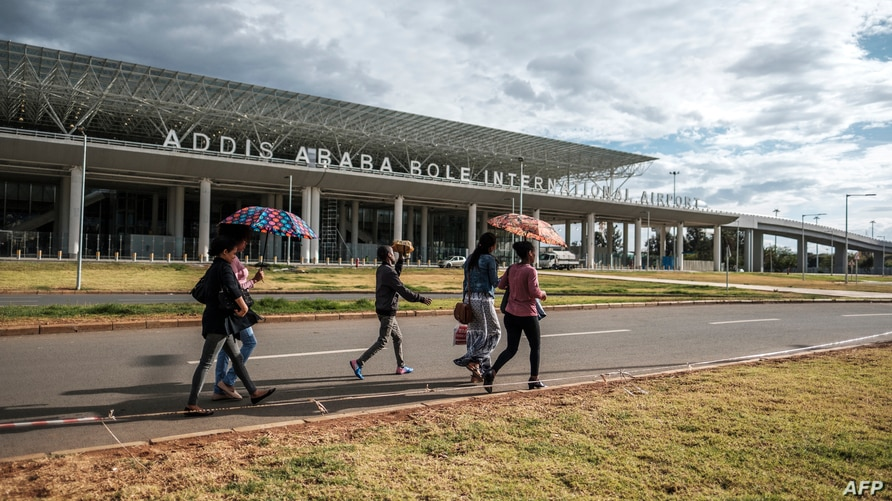 People walk in front of the Bole International Airport, in Addis Ababa, on March 17, 2020. (Photo by EDUARDO SOTERAS / AFP)