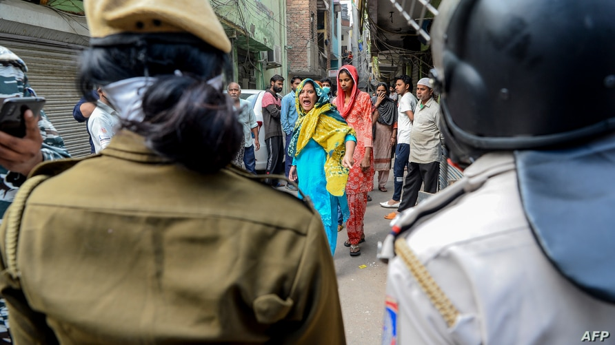 A Muslim woman (C) shouts at security personnel that patrol on the streets in Shaheen Bagh area after removing demonstrators…