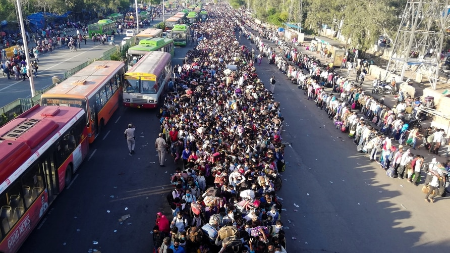 Migrant workers and their family members lineup outsdie the Anand Vihar bus terminal to leave for their villages during a…