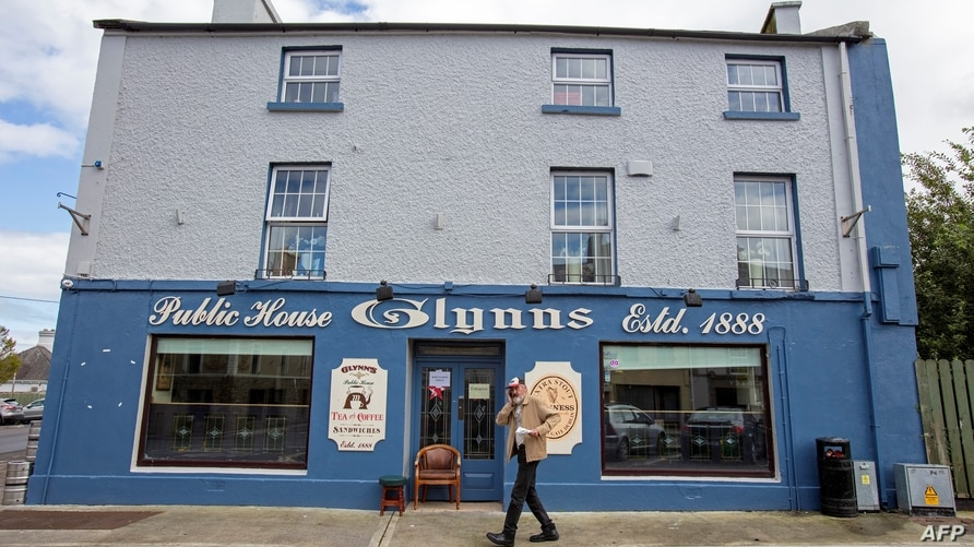 A man speaks on a mobile phone as he passes Glynn's bar, the only open pub in the rural village of Dunmore, west of Ireland, on…