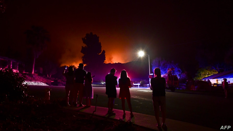 People watch as the Bobcat Fire burns on hillsides behind homes in Arcadia, California on September 13, 2020 prompting…