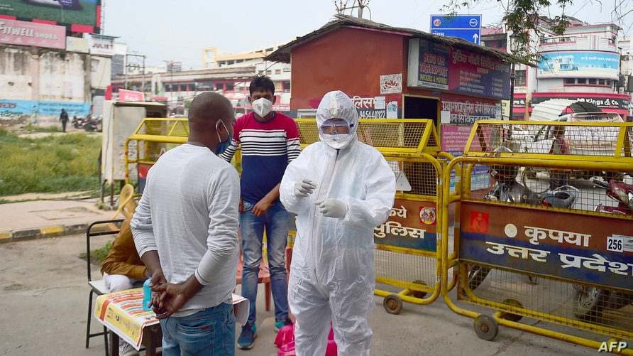 A health worker (R) wearing a Personal Protective Equipment (PPE) suit takes a swab sample from a man for a Rapid antigen tests…