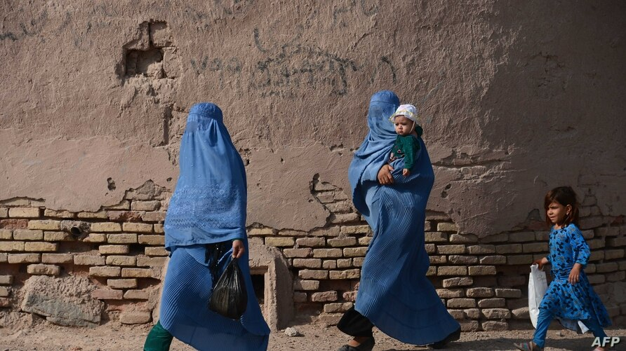 Afghan women walk with their children through the old quarters of Herat on September 20, 2016. (Photo by AREF KARIMI / AFP)