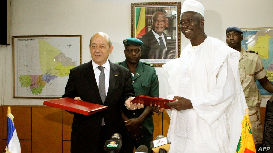 French Defense Minister Jean-Yves Le Drian (L) and his Malian counterpart Bah N'Daw pose on July 16, 2014 in Bamako after…