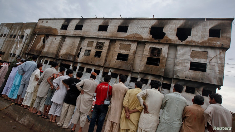 Residents stand outside a garment factory that caught fire the day before, in Karachi September 13, 2012. At least 314 people…