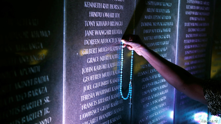 Margaret Achieng Jow, who's daughter Doreen was killed in the 1998 U.S. Embassy in Nairobi bombing, holds a cross on a wall…