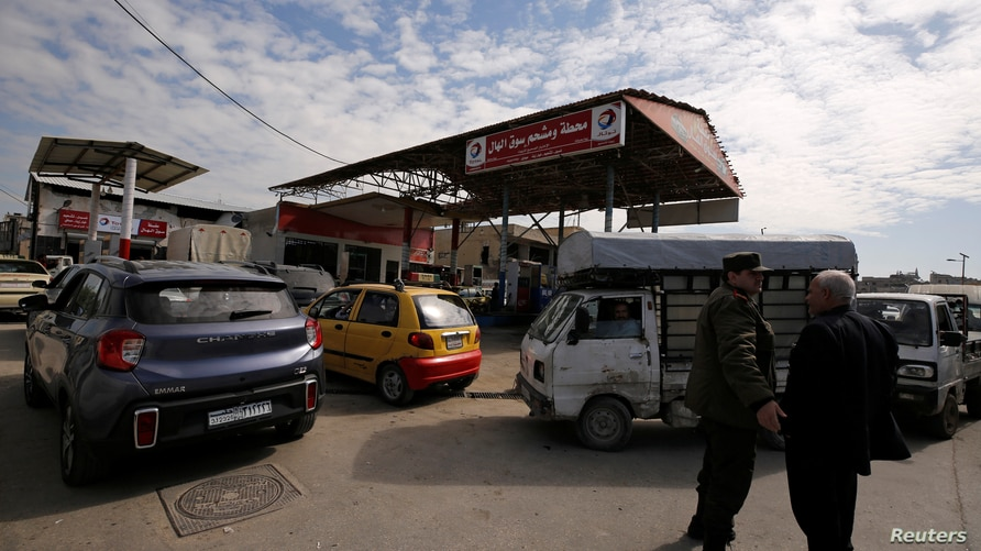 FILE - Cars stand in line at a gasoline station as they wait to fuel up in Aleppo, Syria, April 11, 2019.