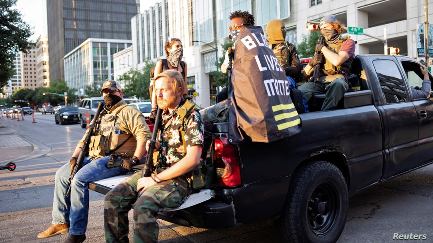 Black Lives Matter protester Jaborey Burns (C) rides around with members of the Texas Guerrillas as they patrol a Black Lives…