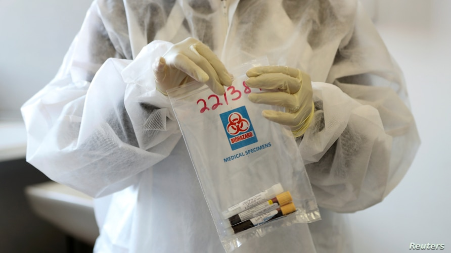 A health worker holds a COVID-19 sample collection kit of a vaccine trials' volunteer, after they were tested for the…