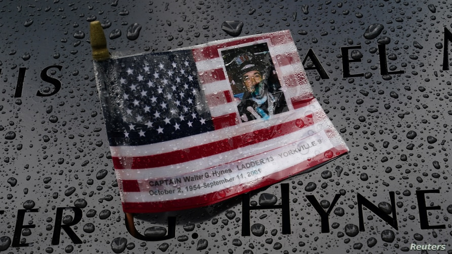 Rain drops rest near a U.S. flag with a picture of Walter Hynes at the south reflecting pool at the National 9/11 Memorial.