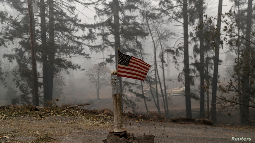 A U.S. flag is taped to the pole at the entrance of a house destroyed by fire in the aftermath of the Beachie Creek fire near…