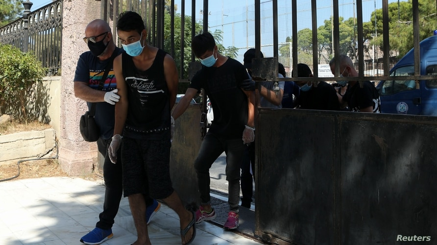 Plainclothes police officers escort four migrants who are detained as suspects for a fire that burned the Moria camp for…