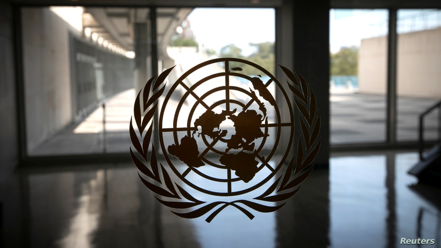 The United Nations logo is seen on a window in an empty hallway at United Nations headquarters.