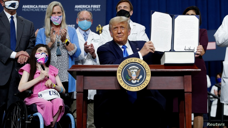 U.S. President Donald Trump displays an executive order he signed at a campaign event on healthcare at Charlotte Douglas…