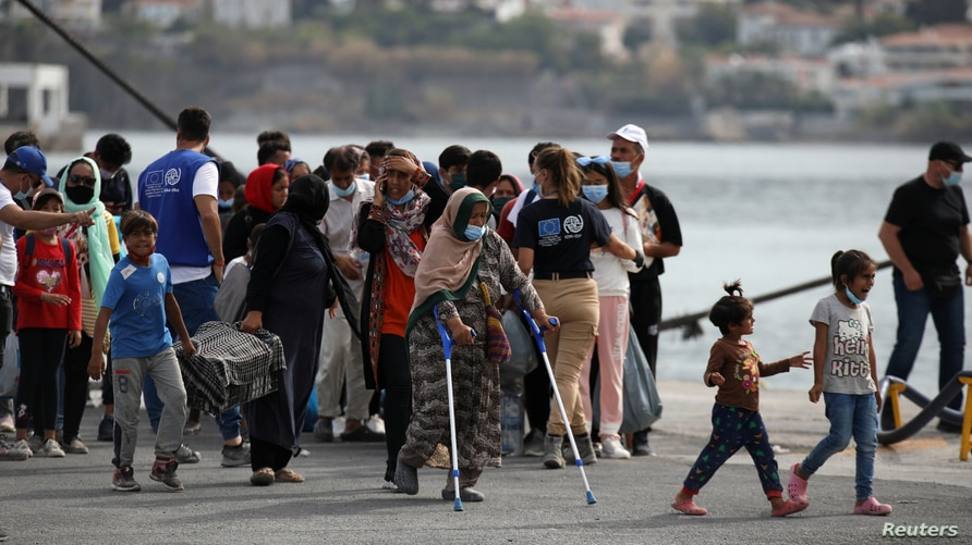Refugees and migrants from the destroyed Moria camp wait to board a ferry that will transfer them to the mainland, at the port…