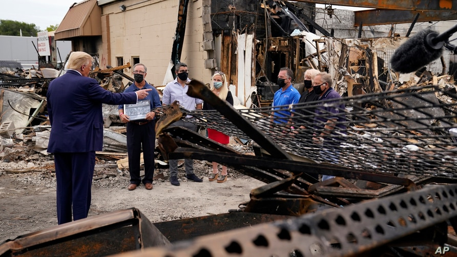 President Donald Trump talks to business owners, Sept. 1, 2020, as he tours an area damaged during demonstrations after a police officer shot Jacob Blake in Kenosha, Wis.