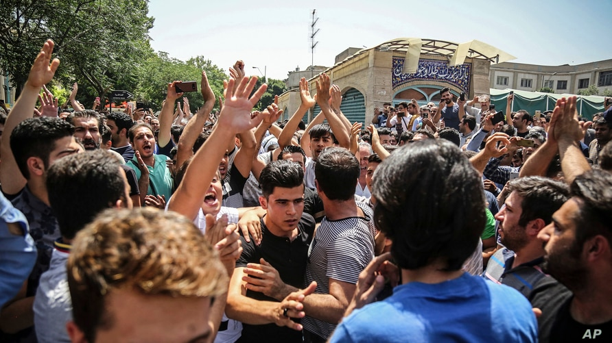 FILE - A group of protesters chant slogans at the main gate of the Old Grand Bazaar, in Tehran, Iran.