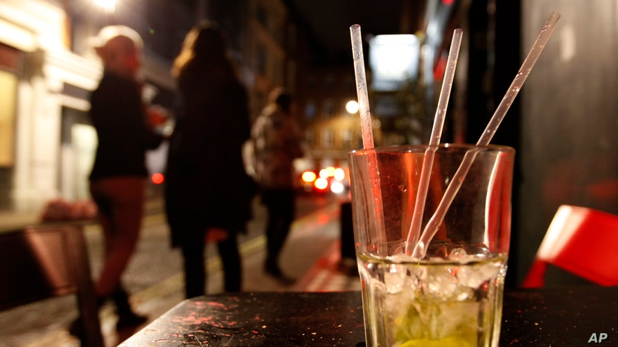 Two young women smoke outside a bar in the central London area of Soho late Friday, April, 21, 2012.  Binge drinking has…