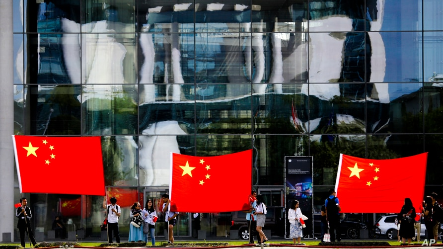 People show Chinese flags in front of the chancellery which is reflected in the facade of a German parliament building prior to…
