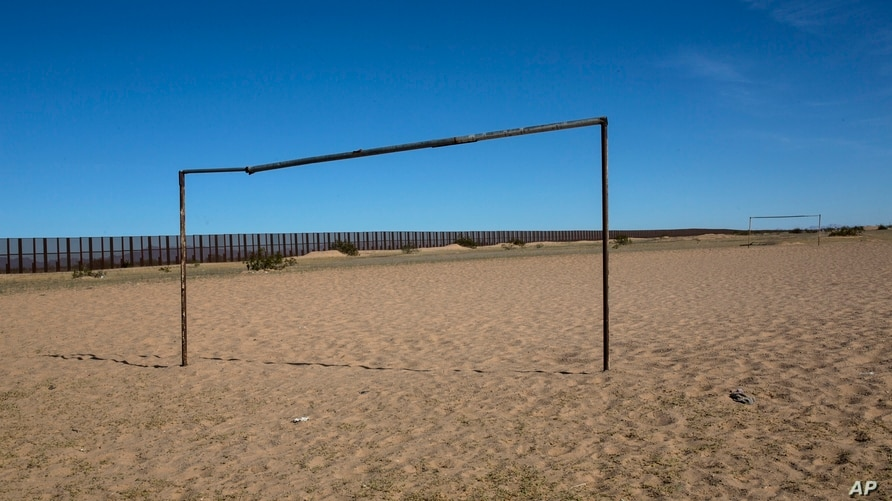 A soccer field is seen next tot the border fence that divides Mexico with the US, at a check point in Baja California, Mexico.