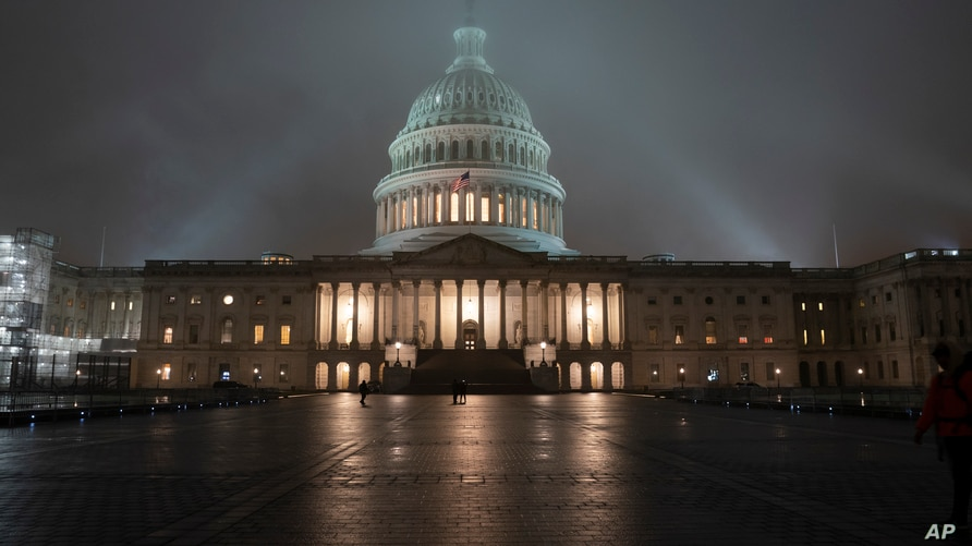 FILE - The U.S. Capitol in Washington is shrouded in mist.
