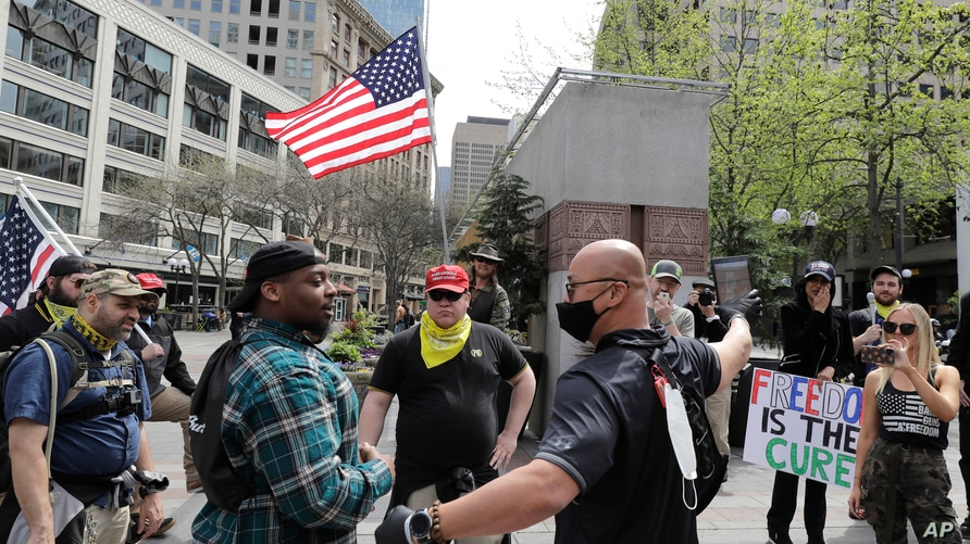 Members of a group wearing shirts with the logo of the far-right Proud Boys group argue with counter protesters during a small…