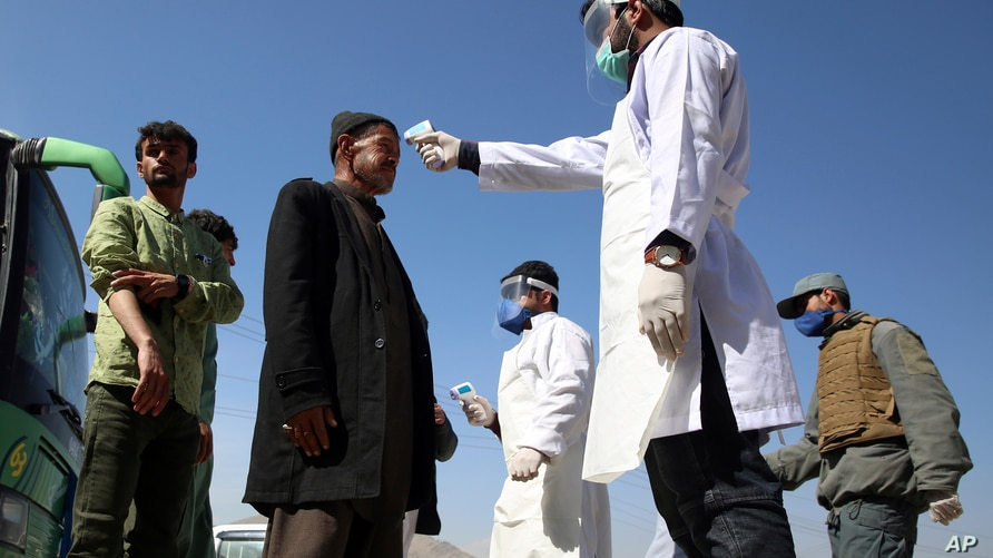 FILE - In this Sunday, March 22, 2020 file photo, health workers measure the temperature of Afghan passengers in an effort to…