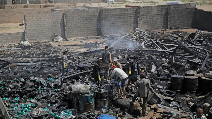 FILE - Workers salvage oil canisters from the wreckage of a vehicle oil store hit by Saudi-led airstrikes in Sanaa, Yemen, July 2, 2020.