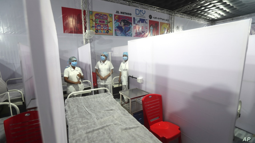 Medical nurses from the Tata Memorial Hospital stand inside a temporary facility created to screen cancer patients for COVID-19…
