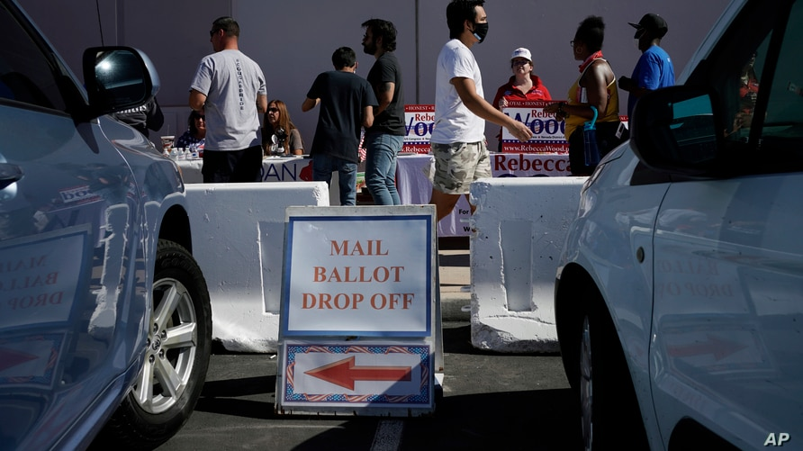 FILE - In this June 9, 2020, file photo, a sign indicates where mail ballots may dropped off as people wait in line at one of a…