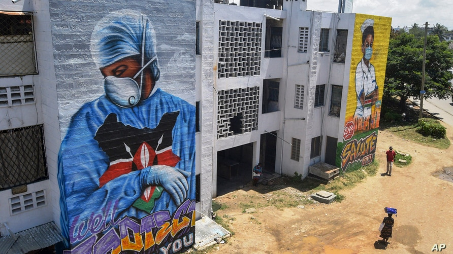 Residents walk in front of informational murals painted on the side of an apartment block about the coronavirus and paying…