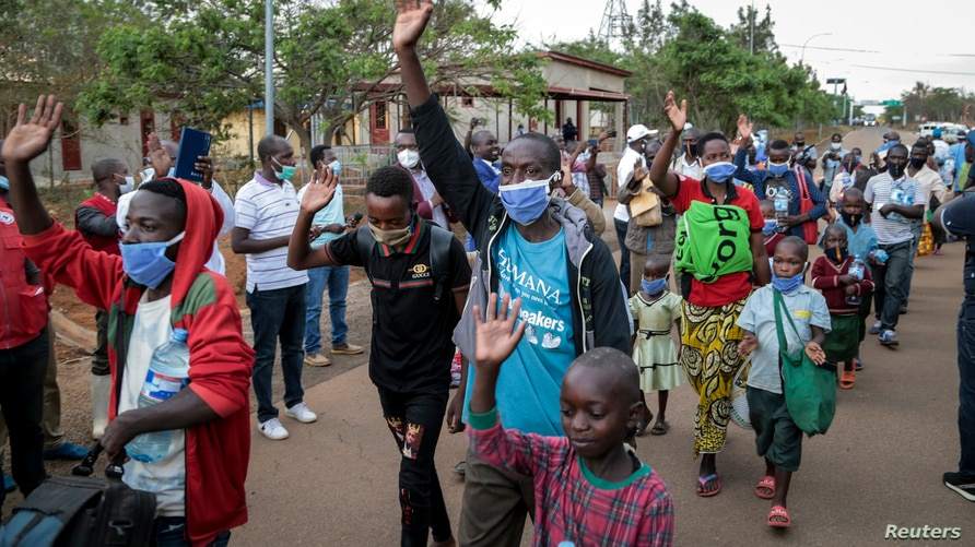 Burundian refugees from Mahama camp in Rwanda wave to gathered media as they arrive back in Gasenyi, Burundi, Aug. 27, 2020.