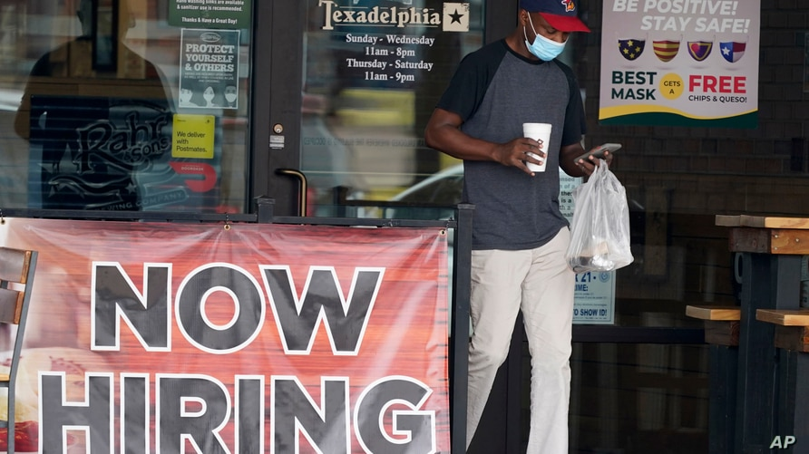 A customer walks past a now hiring sign at an eatery in Richardson, Texas, Sept. 2, 2020.