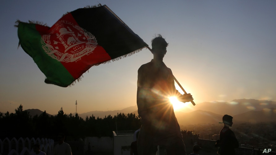 FILE - In this Aug. 19, 2019, file photo, a man waves an Afghan flag during Independence Day celebrations in Kabul, Afghanistan…