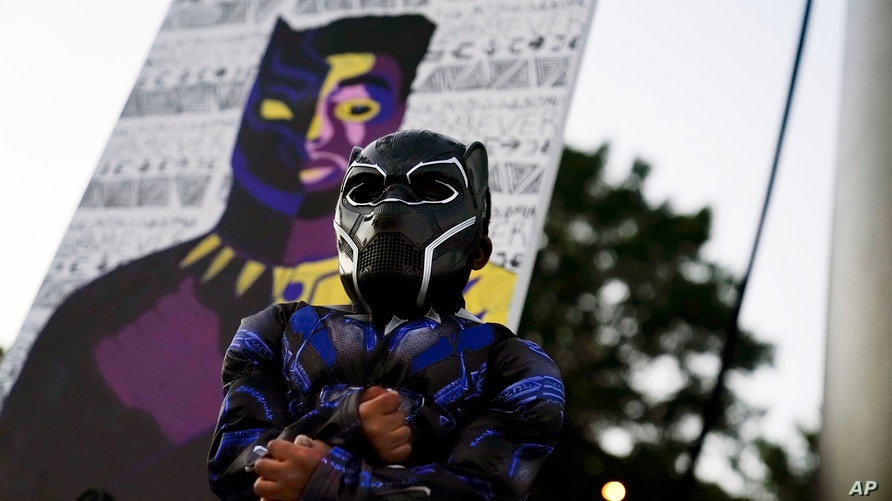 Mason Wilkes, 4, of South Carolina, poses for his father in a Black Panther costume, in front of a painting during a Chadwick…