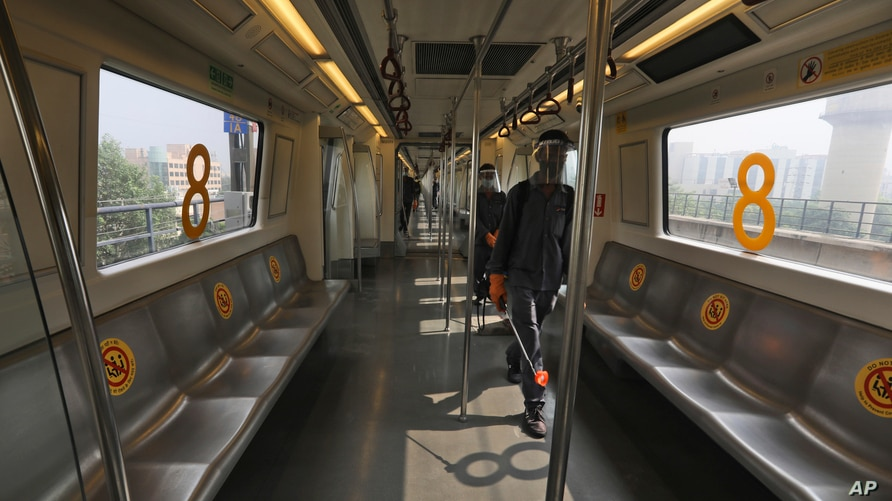 Workers sanitize Delhi metro coaches after it completes a round in Gurugram on the outskirts of New Delhi, India, Sept. 7, 2020.