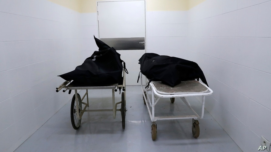 The corpses of two people who died of COVID-19 earlier in the morning lie inside the morgue of the National Hospital Nacional,…