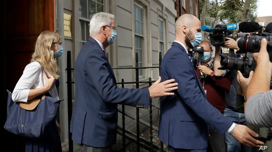 EU Chief negotiator Michel Barnier, centre, is led by security as he leaves the Europa house in London, Sept. 10, 2020.