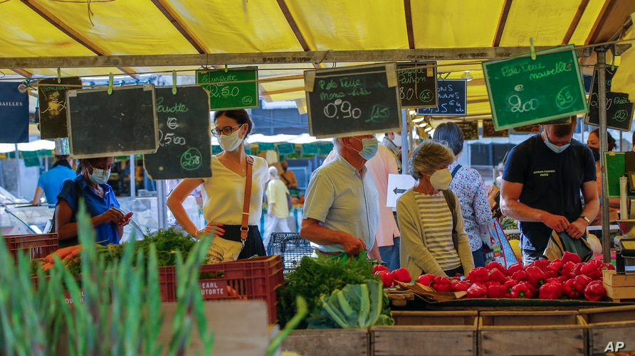 People wearing protective face masks as precaution against the conoravirus shop at a outdoor market in Versailles, west of…
