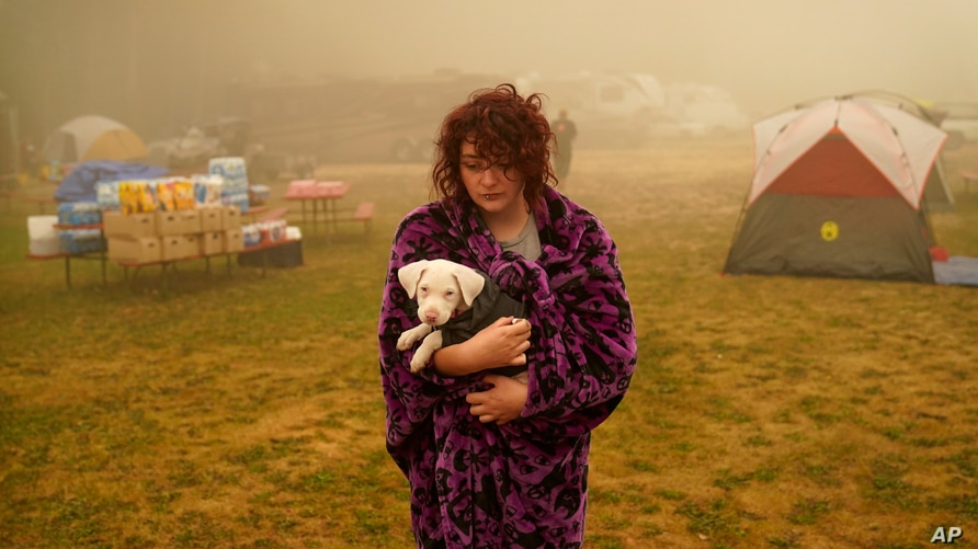Shayanne Summers holds her dog Toph while wrapped in a blanket after several days of staying in a tent at an evacuation center at the Milwaukie-Portland Elks Lodge, Sept. 13, 2020, in Oak Grove, Oregon.