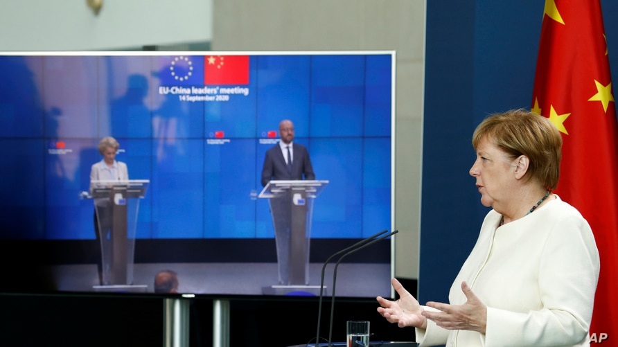 German Chancellor Angela Merkel, right, speaks as she holds a video news conference with European Council President Charles…