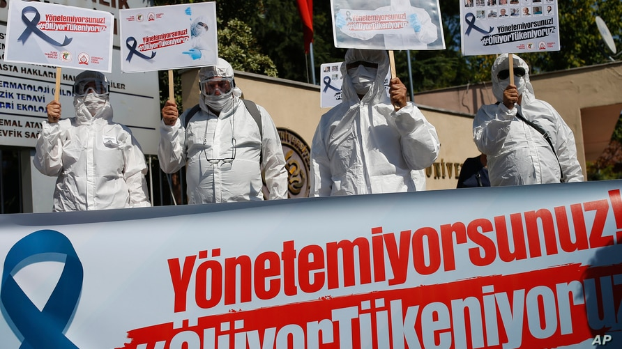 Health workers and doctors wearing personal protective equipment hold a protest against the Turkish goverment's health policy in front of Istanbul University medical faculty, Sept. 15, 2020.