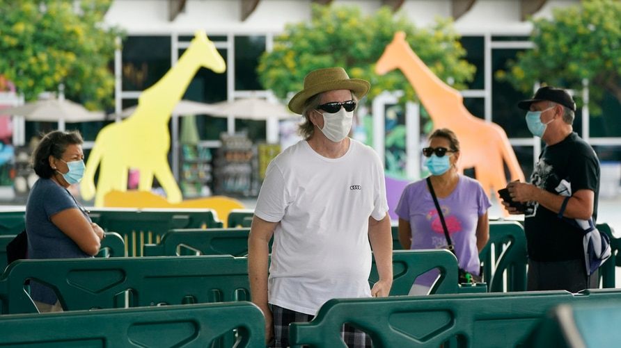 Patrons wearing masks to help prevent the spread of the new coronavirus wait in line to enter Zoo Miami, Tuesday, Sept. 15,…