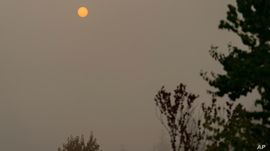 The sun appears orange through wildfire smoke, Wednesday, Sept. 16, 2020, in Olympia, Wash. The smoke from dozens of wildfires…