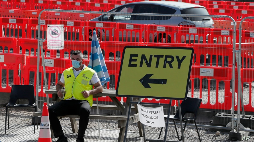 A staff member waits at the entrance to nearly empty lanes of a Covid-19 drive thru testing facility at Twickenham stadium in…