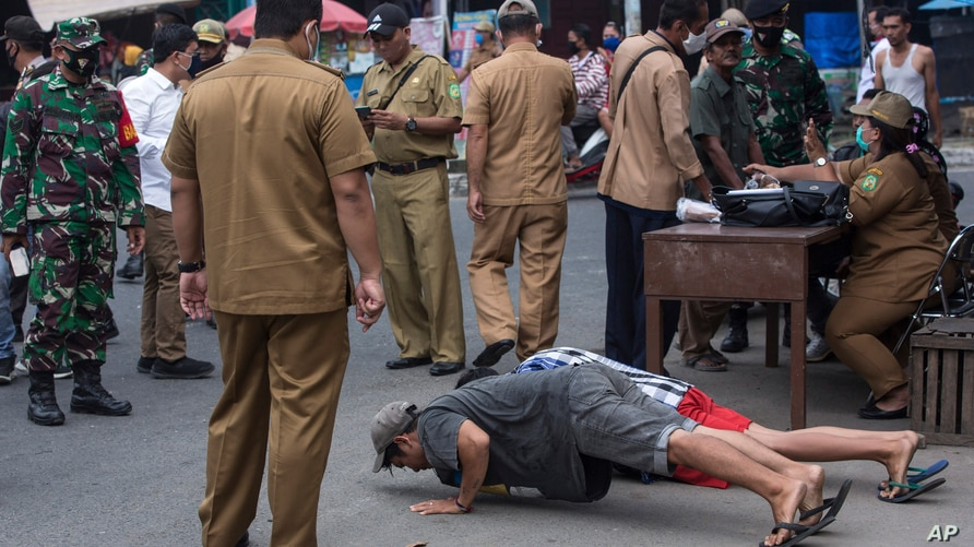 A public order agency officer watches over as men do push ups as a punishment for violating the city regulation requiring…