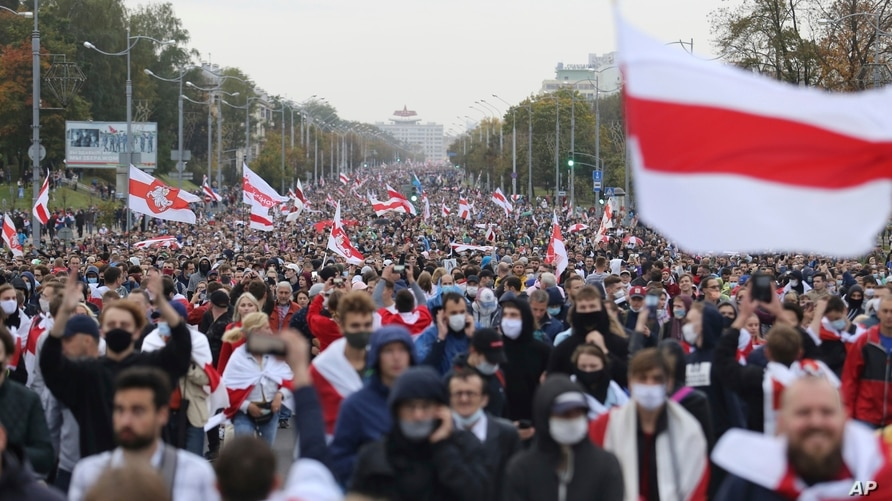 People with old Belarusian national flags march during an opposition rally to protest the official presidential election results in Minsk, Belarus, Sept. 27, 2020.